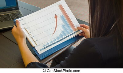Young dark-haired woman doing her work looking at some diagrams