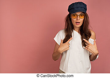 Young dark-haired woman with yellow eyeglasses and dark cap points at herself opening eyes widely, pink background