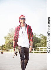 Young dark skinned boy holding skateboard