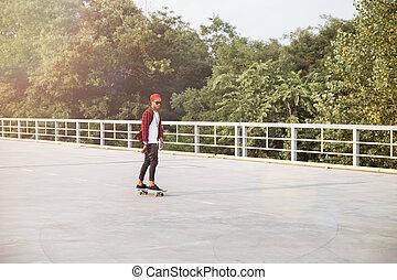 Young dark skinned boy skateboarding