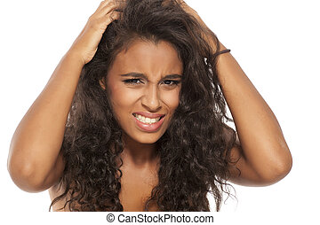 young dark skinned girl has itching in her hair