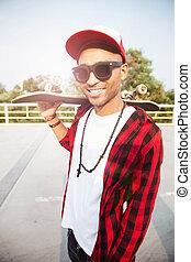 Young dark skinned guy wearing sunglasses holding skateboard