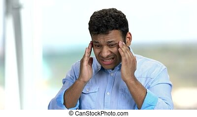Young dark-skinned man suffering from headache. Stressed Indian man massaging his temples because of terrible migraine. Abstract blurred background.