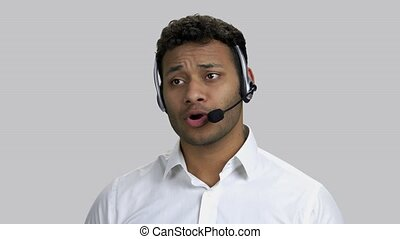 Young dark-skinned man talking with someone through headset mic. Grey isolated background.