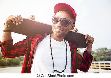 Young dark skinned man wearing sunglasses holding skateboard