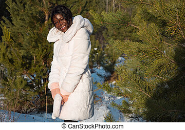 Young dark-skinned woman in a white fur coat among pine trees in winter