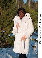 Young dark-skinned woman in a white fur coat in a winter forest
