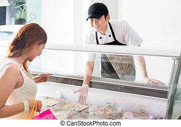 Young deli assistant serving a customer