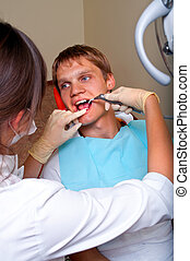 Young dentist giving a treatment to her patient