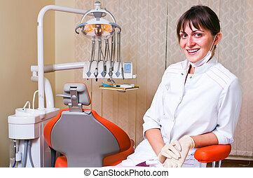 Young dentist in her office looking at the viewer