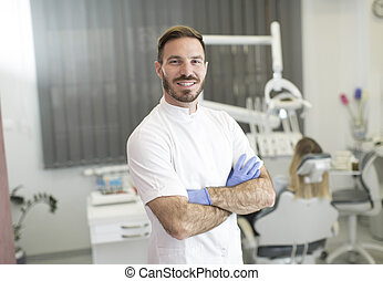 Young dentist posing in dental office