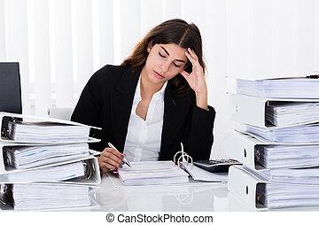 Depressed Businesswoman Checking Invoice