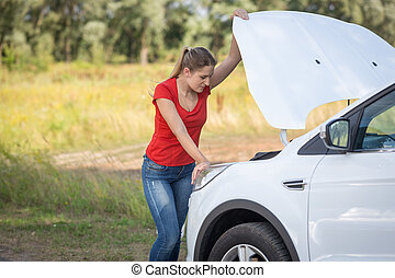 Young depressed woman looking on the engine of broken car in field