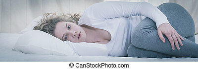 Young depressed woman lying alone in her bed
