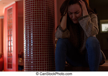Young depressed woman sitting on steps at home and crying