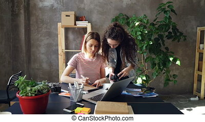 Young designer is drawing images in notebook sitting at table while female photographer is coming to her with camera. Women start discussing project and watching photos on screen.