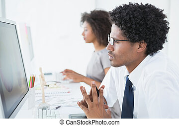 Young designer looking at computer at his desk