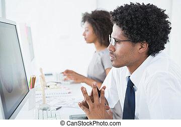 Young designer looking at computer at his desk
