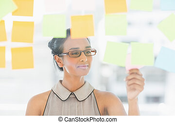 Young designer looking at sticky notes on window