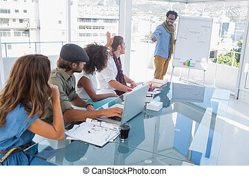 Young designer presenting a flow chart to colleagues during...