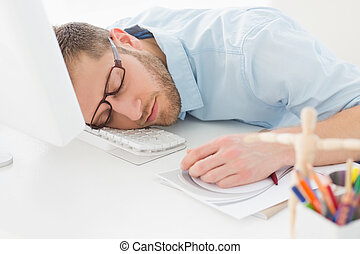 Young designer sleeping at his desk  in creative office