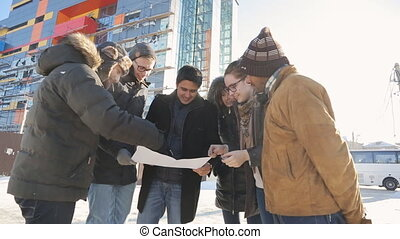 Young designers stand on street and discuss plan of construction