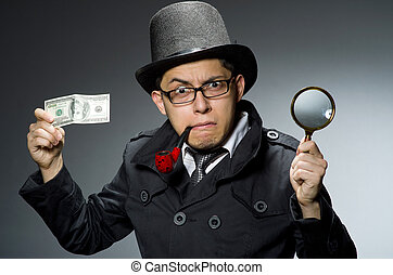 Young detective in black coat with money against gray