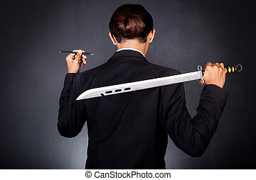 Young determined businessman in suit holding sword