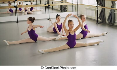 Young diligent ballet students are doing leg splits and...