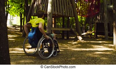 Young disable man in a wheelchair in the park