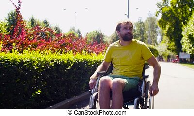 Young disable man in wheelchair in the park - Dolly shot....