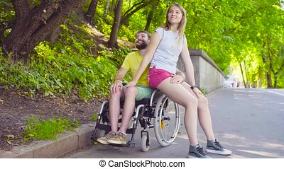Young disable man on a walk in the park with his wife