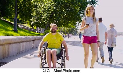 Young disable man on a walk near the river with his wife -...