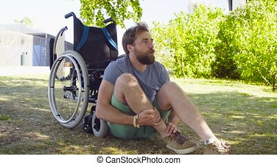 Young disable man trying to sit down in a wheelchair - Happy...
