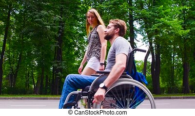 Young disable man walking in the park with his wife