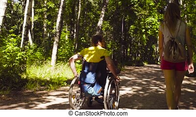 Young disable man with his wife on a walk in the park