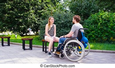 Young disable man with his wife sitting in the park