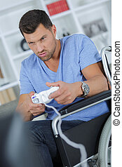 young disabled handsome man playing video games