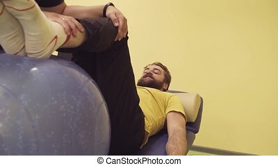 Young disabled man doing exercises at the rehabilitation...