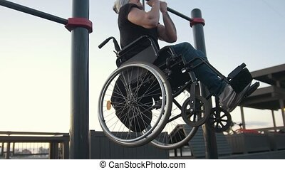 Young disabled man in wheelchair engaged on the crossbar...