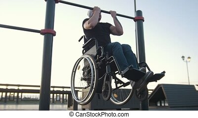 Young disabled man in wheelchair engaged on the crossbar outdoors