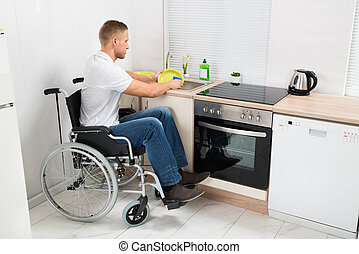 Man On Wheelchair Washing Dishes - Young Disabled Man On...