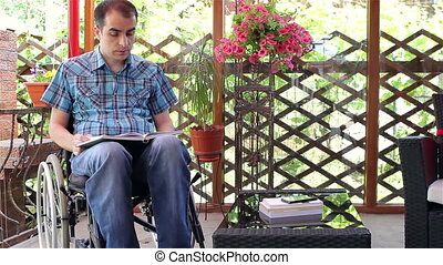 Young disabled man reading book
