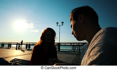 Young Disabled Man Talking To A Young Woman On The Waterfront At Sunset