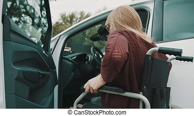Young disabled person getting out from the car in her wheelchair. . High quality 4k footage