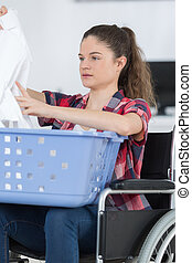 young disabled woman in wheelchair doing the laundry