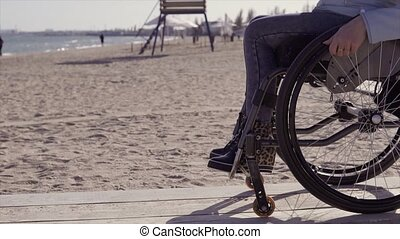 Young disabled woman in wheelchair moving by the wooden ramp...