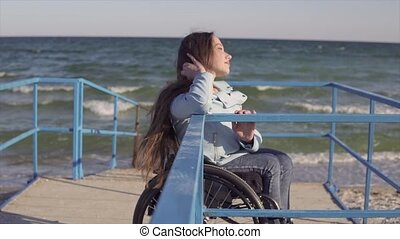 Young disabled woman in wheelchair resting near the sea on...