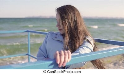 Young disabled woman in wheelchair resting near the sea on the ramp for people with disabilities