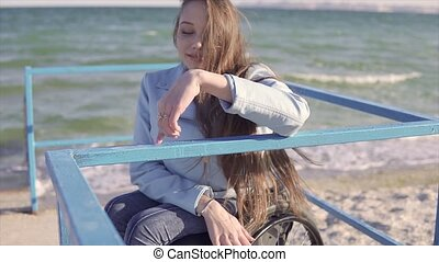 Young disabled woman in wheelchair shows fingers step...
